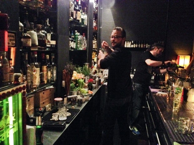 Barkeeper vor Opfergaben an den Alkoholgott.